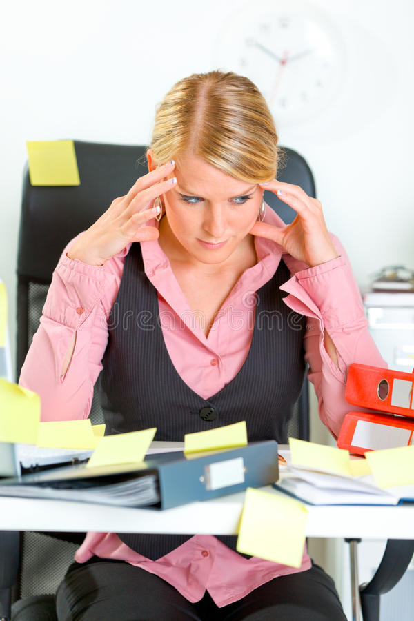 Tired business woman sitting at workplace stock images