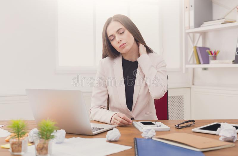Young business woman with neck ache in office. Tired business woman suffering from ache and massaging her neck in office royalty free stock photo