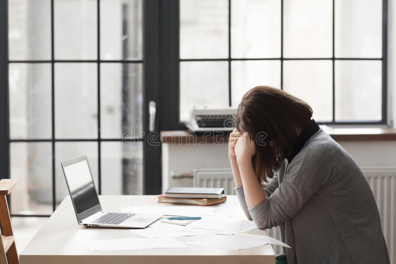 Tired business woman at workplace in office royalty free stock image
