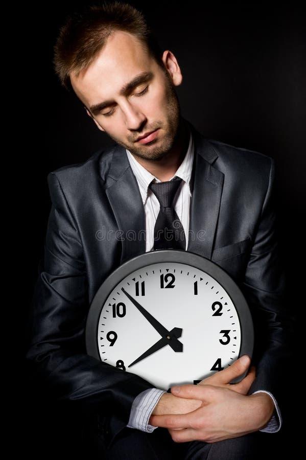 Tired businessman. Tired sleeping businessman holding clock, over black stock photo