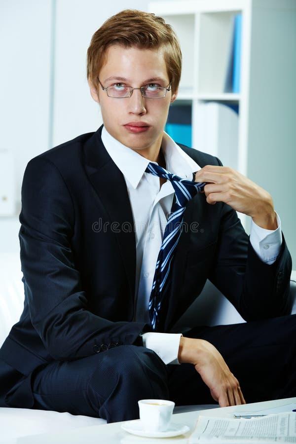 Tired businessman. Portrait of tired businessman untying necktie stock photo