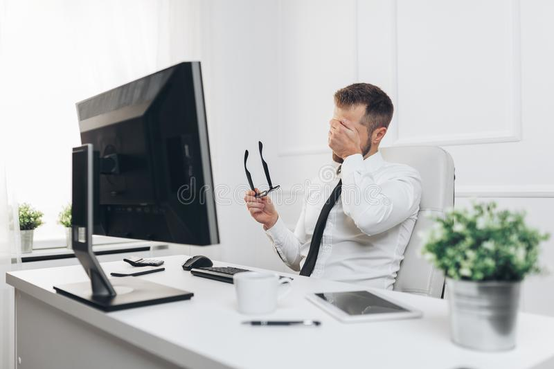 Tired businessman from heavy workload. Sitting at the desk stock photos