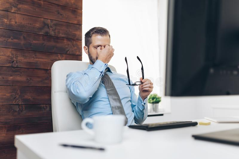 Tired businessman from heavy workload. Sitting at the desk royalty free stock images
