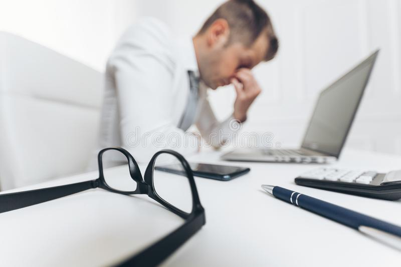 Tired businessman from heavy workload. Sitting at the desk stock photo