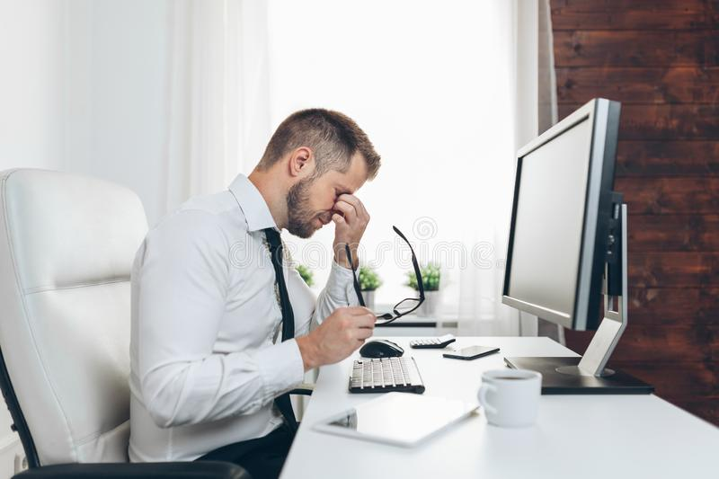 Tired businessman from heavy workload. Sitting at the desk royalty free stock photography