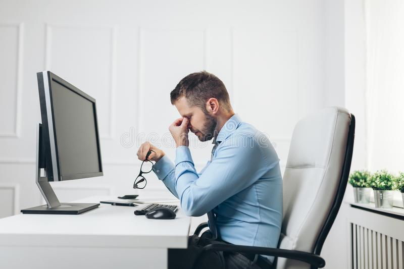 Tired businessman from heavy workload. Sitting at the desk stock photography