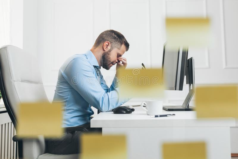 Tired businessman from heavy workload. Sitting at the desk royalty free stock photo