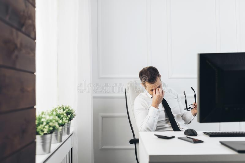 Tired businessman from heavy workload. Sitting at the desk royalty free stock photos