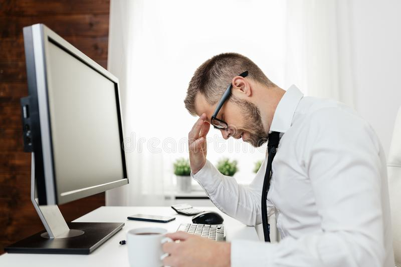 Tired businessman from heavy workload. Sitting at the desk stock image