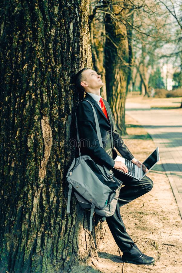 Tired businessman near the tree. freelancer rests and rejoices in the sun.  stock image