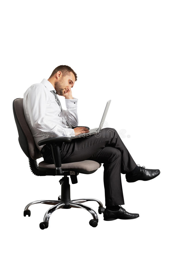 Tired businessman sitting on office chair. And looking at laptop stock photo