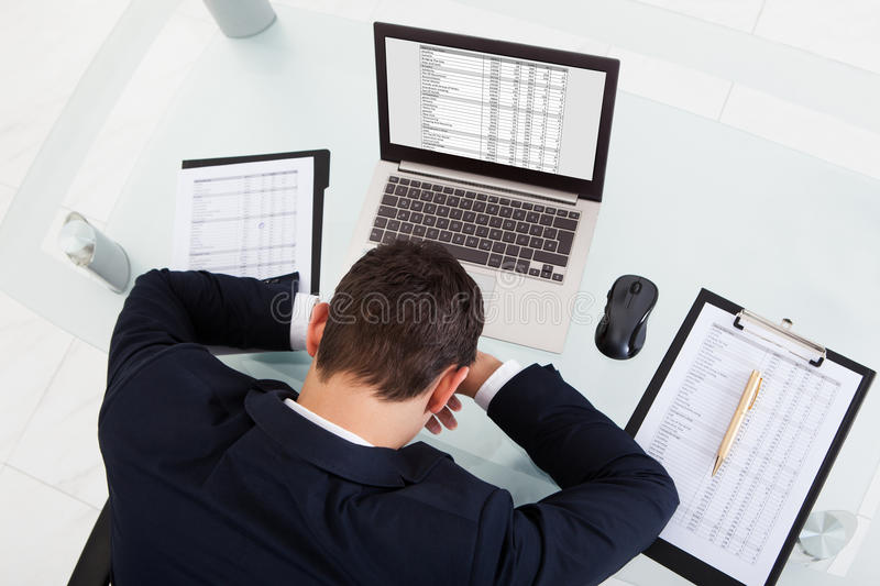 Tired businessman sleeping while calculating expenses in office. High angle view of tired businessman sleeping while calculating expenses at desk in office stock image