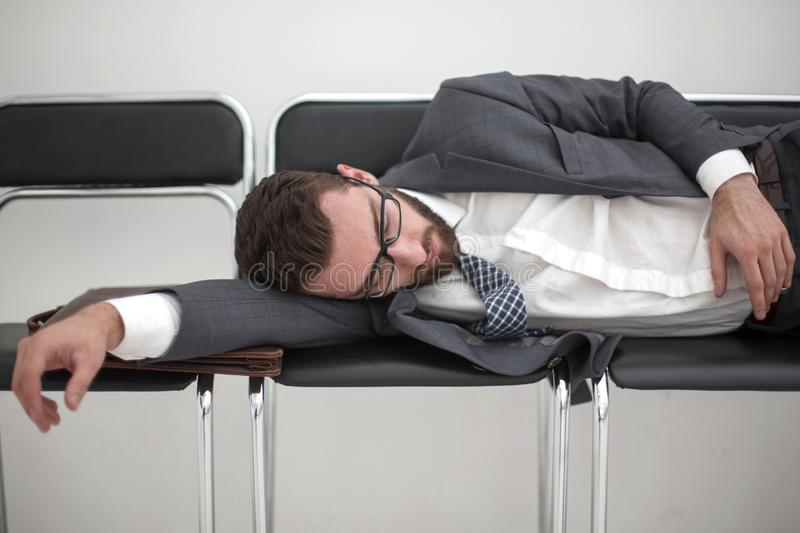 Tired businessman sleeping on chairs in the office hallway royalty free stock image