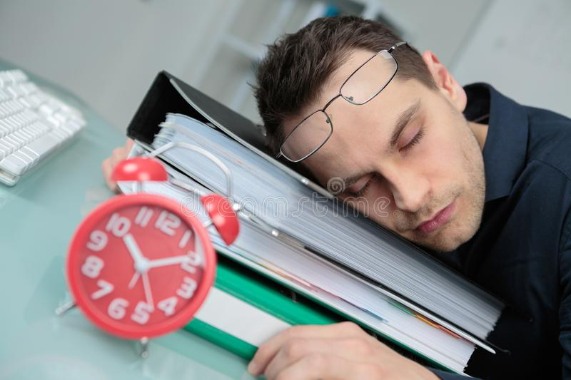 Tired businessman sleeping on files stock image