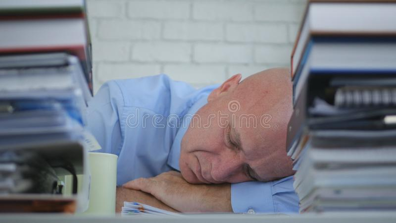 Tired Businessman Sleeping With Head On The Table In Office Room royalty free stock image