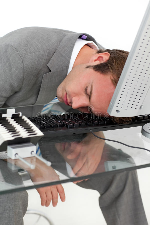 Tired businessman sleeping on his desk. Against a white background royalty free stock photo