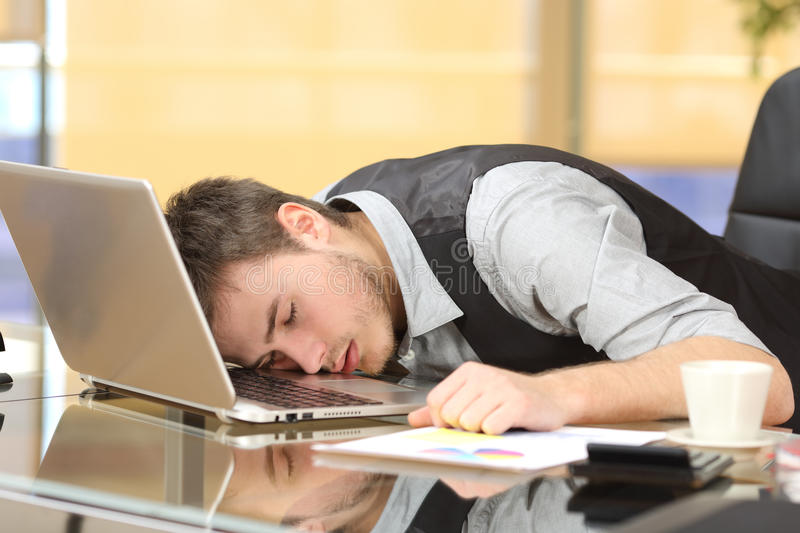 Tired businessman sleeping over a laptop at job. Tired overworked businessman sleeping over a laptop in a desk at job in his office stock photos