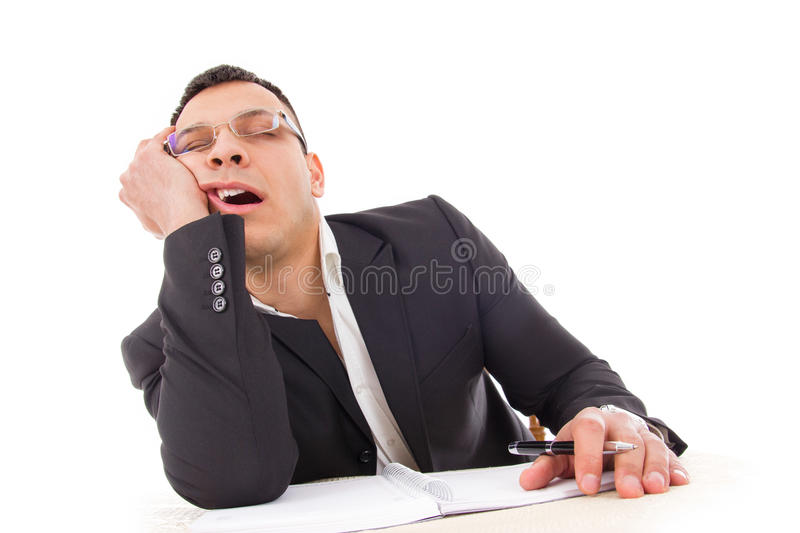 Tired businessman sleeping at work yawning. Tired businessman yawning and sleeping at work with pen in hand royalty free stock photo