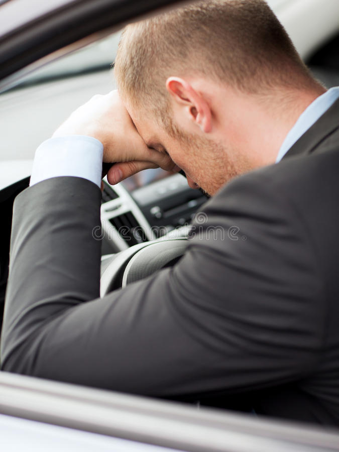 Tired businessman or taxi car driver stock image