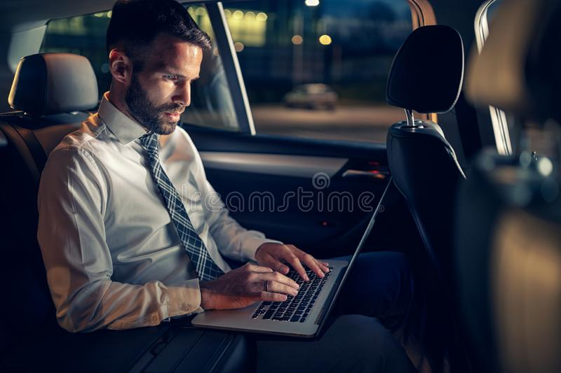 Tired businessman working late in car on laptop. In back seat stock image