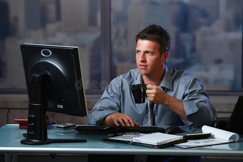 Tired businessman working late in office stock image