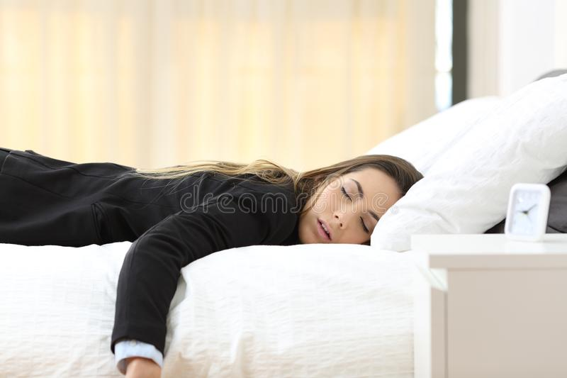 Tired businesswoman on a bed after a bad day. Tired businesswoman lying on a bed after a bad day stock photography