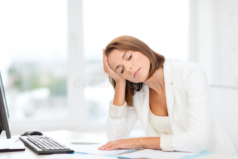 Tired Businesswoman With Computer And Papers Stock Photo