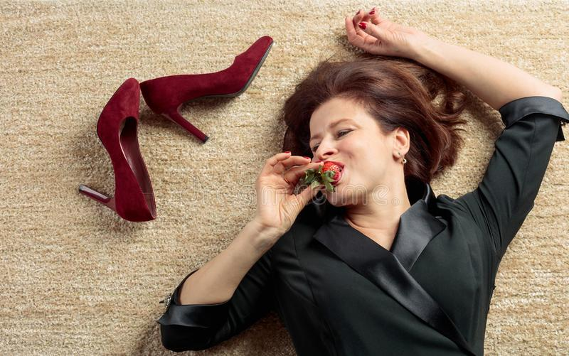 Tired businesswoman lying on the carpet and eating strawberries royalty free stock images