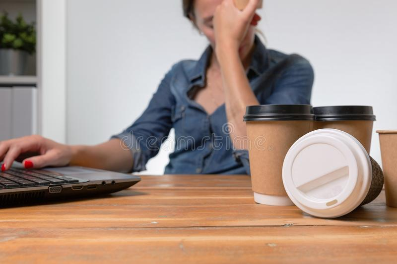 Tired businesswoman in the office with many to go coffee cups on the table royalty free stock photo