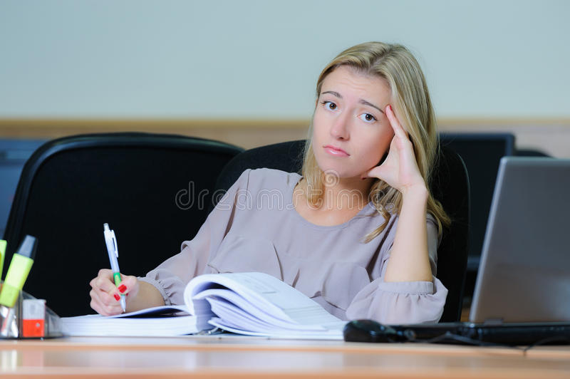 Tired businesswoman at the office. Tired young woman sitting at the table with a book, laptop, with pen in hand at the office stock photo