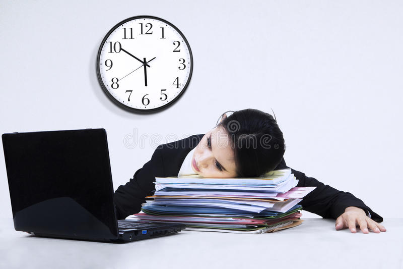 Tired businesswoman overworked 1. Portrait of overworked business woman take a rest on a pile of documents stock photo