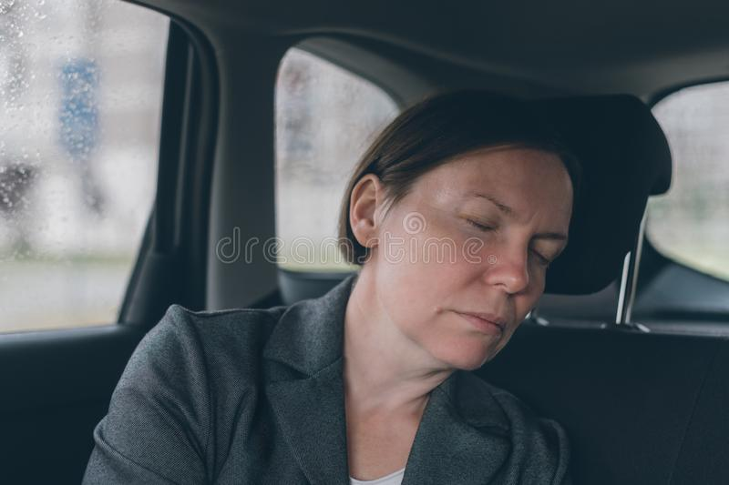 Tired businesswoman sleeping at car back seat stock photography