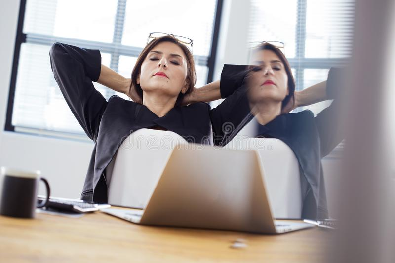Tired businesswoman stretching in office stock photos