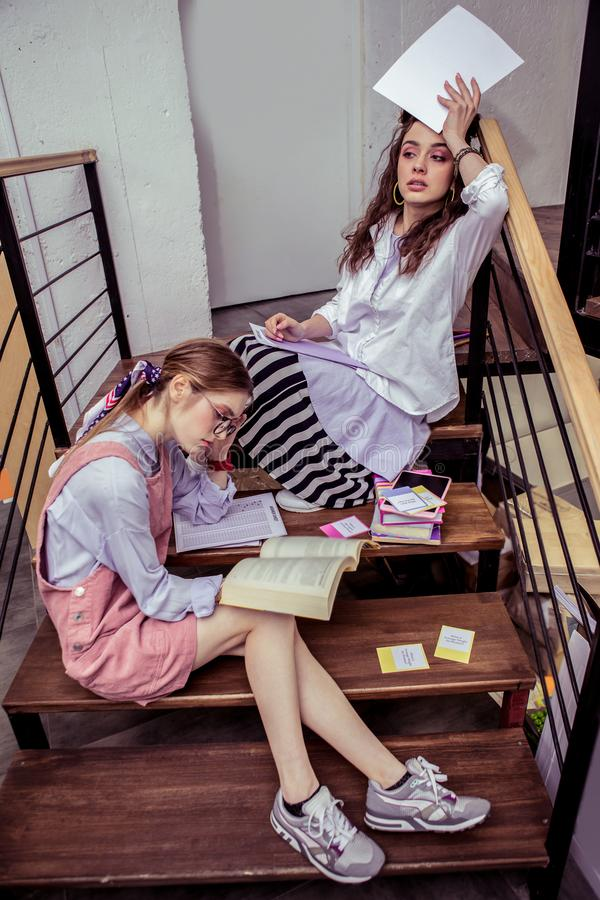 Tired busy girls inspecting materials and papers in co-working space royalty free stock photo