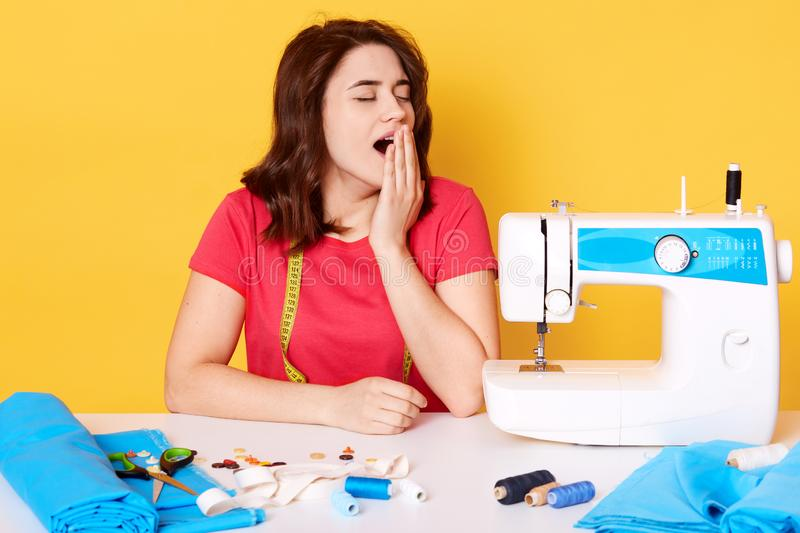 Tired busy seamstress sits at table with sewing machine, closes her eys, yawns, having many things to do, wearing casual red t royalty free stock image