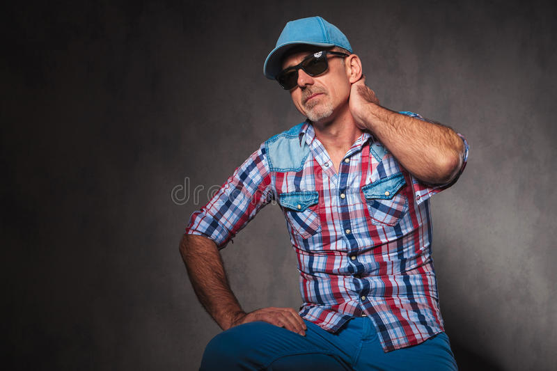 Tired casual old man wearing baseball hat and sunglasses stock image