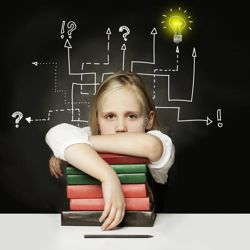 Tired child with books thinking on chalkboard. royalty free stock photos