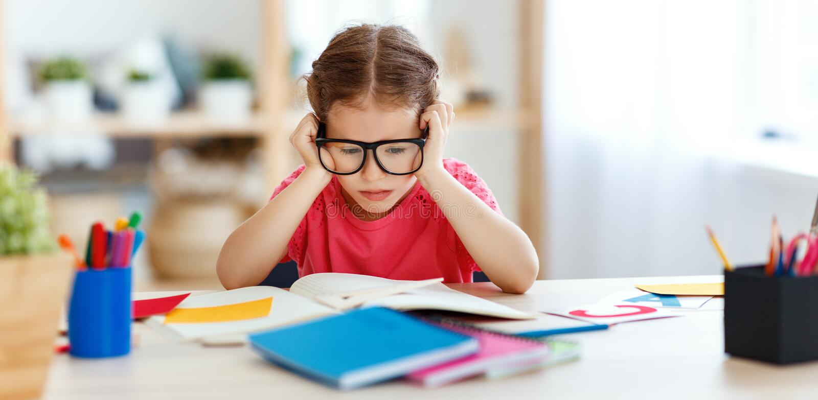 Tired child girl   doing her homework  at home. Tired child girl doing her homework, studied writing and reading  at home stock photos