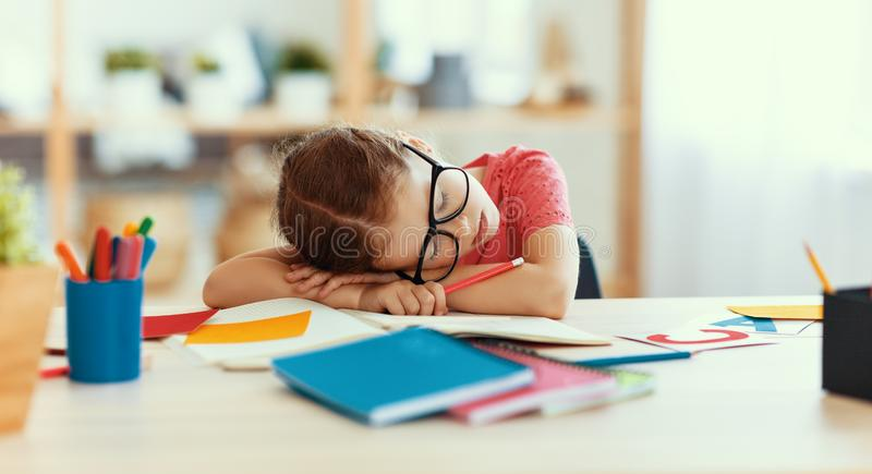 Tired child girl fell asleep when she did her homework  at home. Tired child girl fell asleep when she did her homework, studied writing and reading  at home stock photos