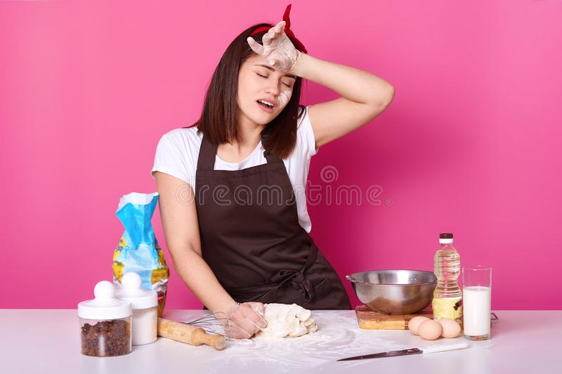 Tired cook stands with closed eyes at table in kitchen, keeps hand on forehead, spends herself with kneading dough. Young female royalty free stock photo