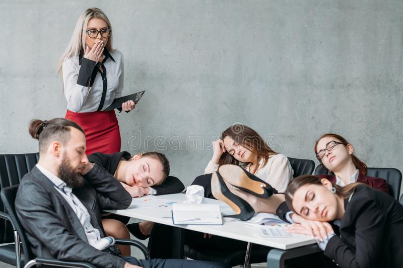 Tired corporate personnel sleep desk overworking. Tired corporate personnel. Overworking concept. Colleague looking at team members sleeping on desk and chairs royalty free stock image