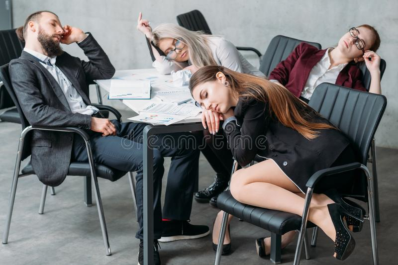 Tired corporate personnel sleep desk overworking. Tired corporate personnel. Overworking concept. Business team members sleeping on desk and chairs stock image