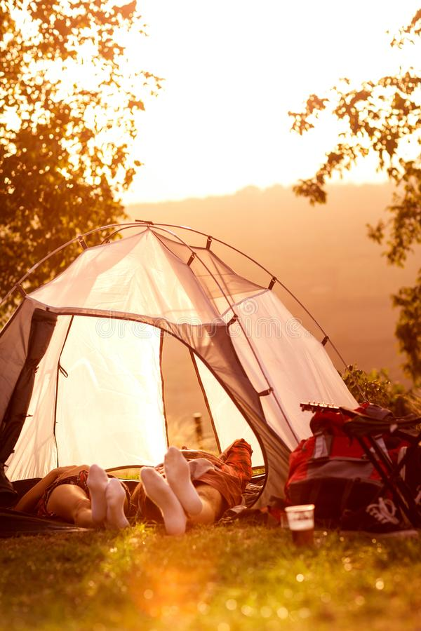 Tired couple lying in tent. Tired couple lying in tent, relaxing after party on music festival royalty free stock image