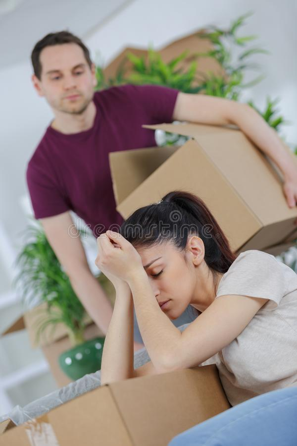 Tired couple sitting among carton boxes stock photos