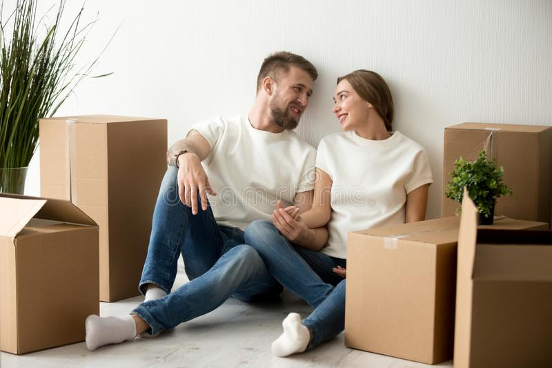 Tired couple sitting leaning back against wall in new apartment stock images