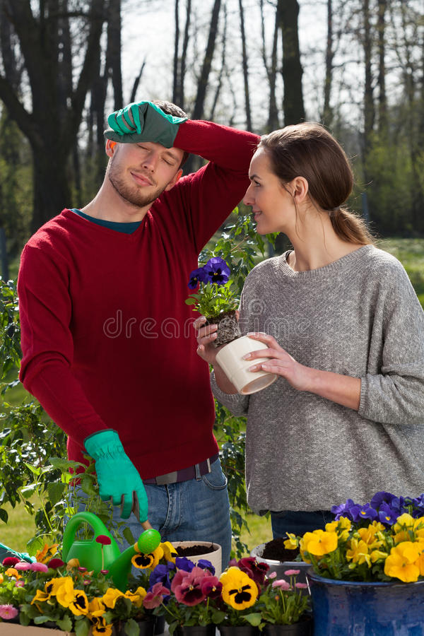 Tired couple during working in the garden. Vertical stock image