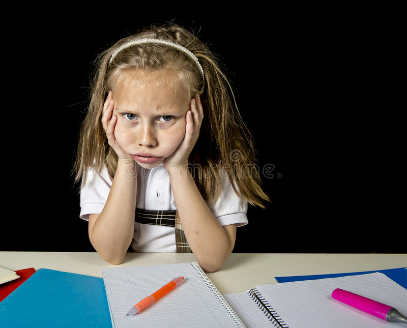 Tired cute junior schoolgirl with blond hair sitting in stress working doing homework looking bored. Sad and tired cute junior schoolgirl with blond hair sitting stock images