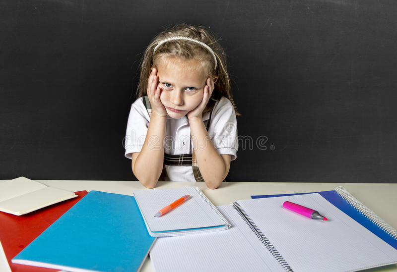 Tired cute junior schoolgirl with blond hair sitting in stress working doing homework looking bored. Sad and tired cute junior schoolgirl with blond hair sitting stock photo