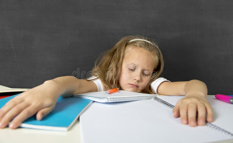 Tired cute junior schoolgirl with blond hair sitting in stress working doing homework looking bored. Sad and tired cute junior schoolgirl with blond hair sitting royalty free stock image
