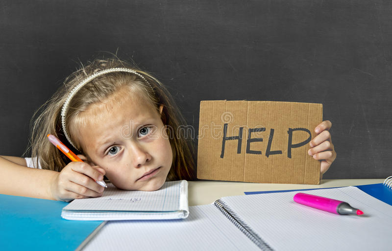 Tired cute junior schoolgirl with blond hair sitting in stress working doing homework looking bored. Sad and tired cute junior schoolgirl with blond hair sitting royalty free stock photos